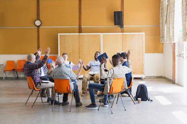 Men praying with arms raised in prayer group in community center — Stock Photo