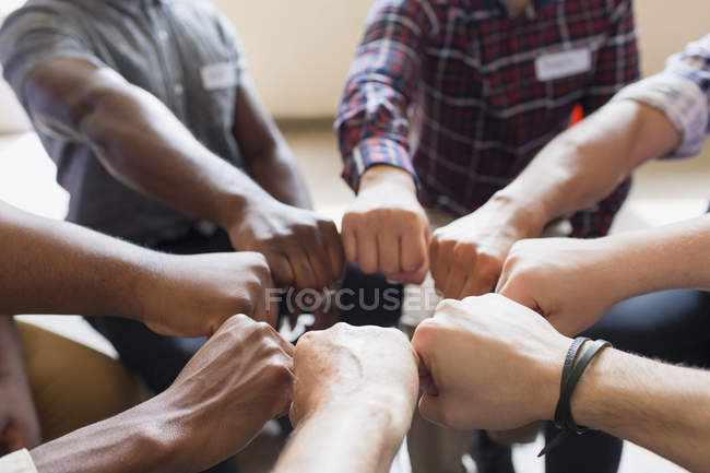 Men joining fists in circle in group therapy — Stock Photo