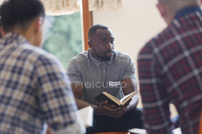 Attentive young man with bible in prayer group — Stock Photo