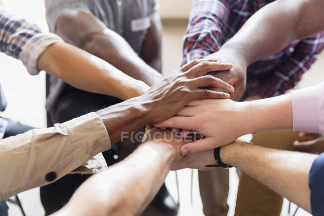 Men joining hands in huddle — Stock Photo