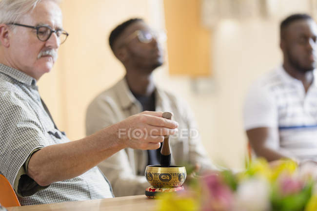 Man using singing bowl in meditation group — Stock Photo