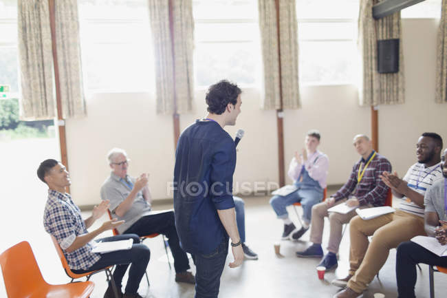Man with microphone speaking to group in community center — Stock Photo