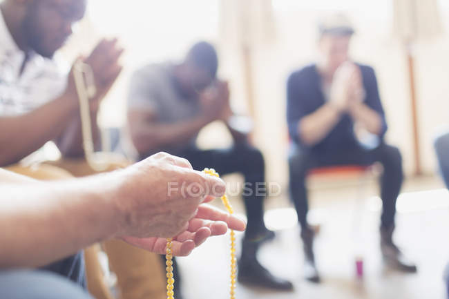 Men praying with rosaries in prayer group — Stock Photo