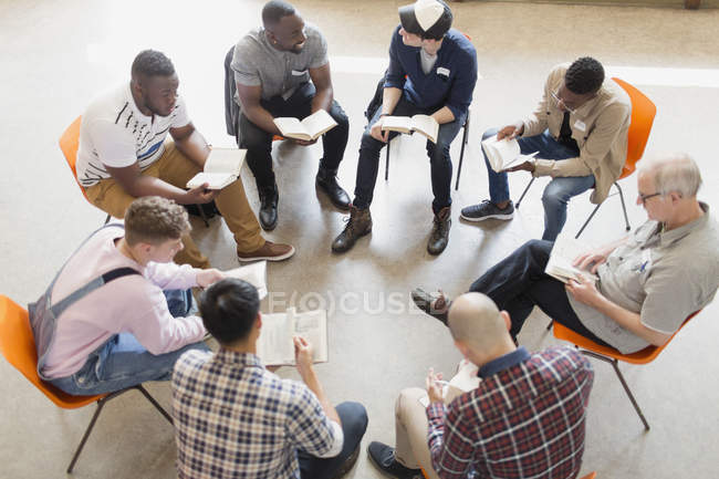 Men reading and discussing bible in prayer group circle - foto de stock