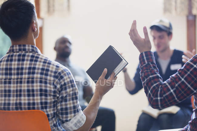 Men with bible praying with arms raised in prayer group — Stock Photo