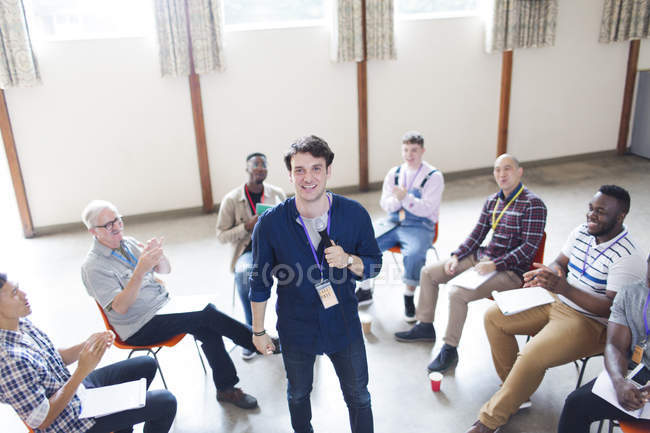 Men clapping for speaker in group therapy - foto de stock