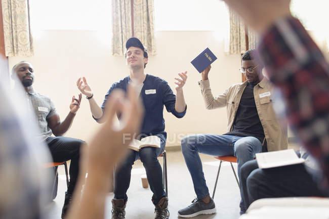 Мужчины с Библии, молясь с поднятыми в молитве группы — стоковое фото
