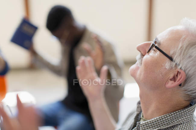 Senior man with head back praying in prayer group — Stock Photo