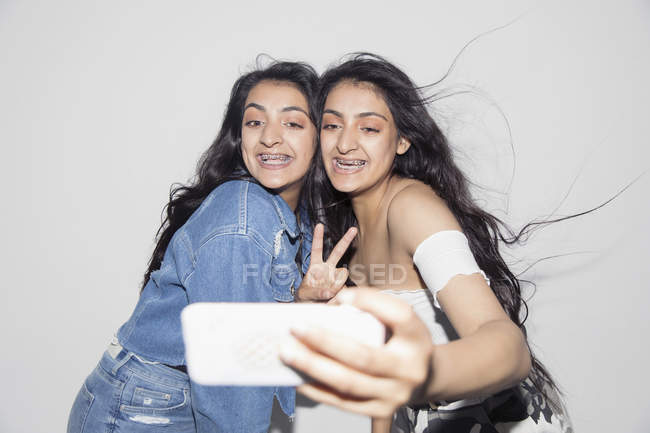 Carefree teenage twin sisters with braces taking selfie with smart phone — Stock Photo