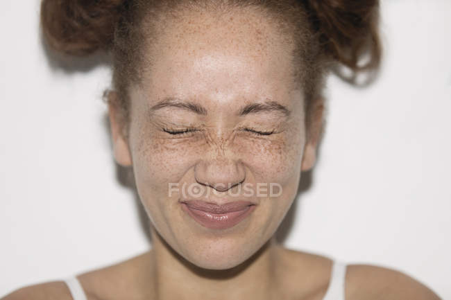 Portrait playful young woman with freckles squeezing eyes shut — Stock Photo