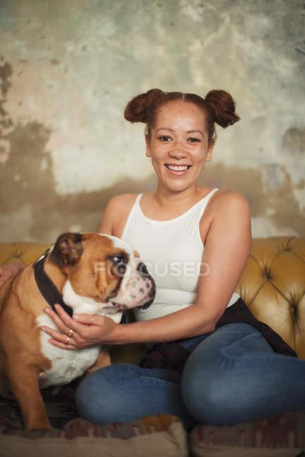 Портрет улыбающейся молодой женщины, ласкающей собаку на диване — стоковое фото