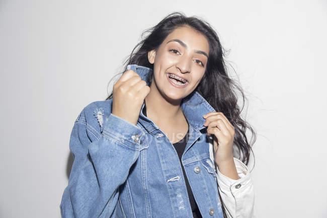 Портрет счастливой, уверенно девушка с брекетами носить джинсовые куртки — стоковое фото