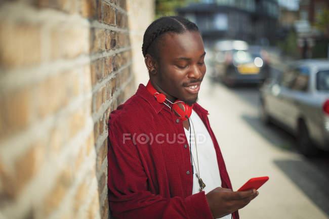 Smiling teenage boy with headphones using mp3 player on urban sidewalk — Stock Photo