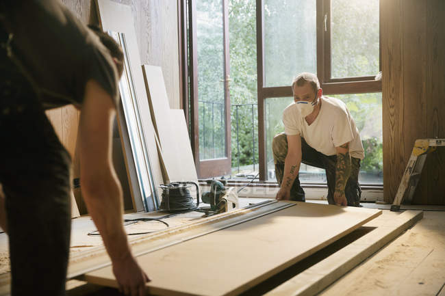 Trabalhadores da construção civil levantamento de placa de madeira em casa — Fotografia de Stock