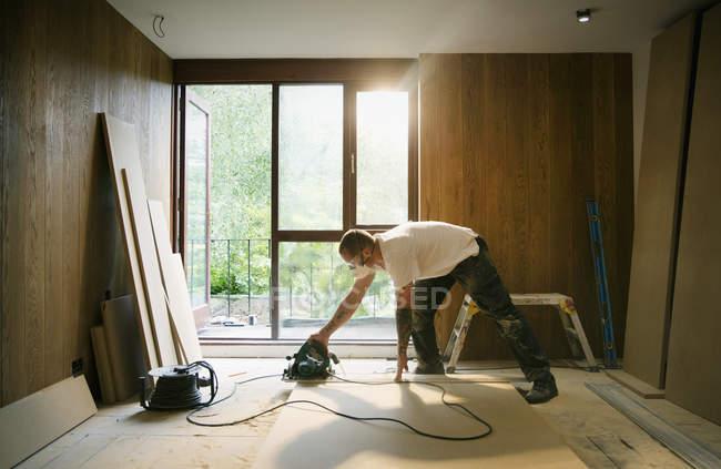 Trabajador de la construcción usando sierra eléctrica para cortar madera en casa - foto de stock