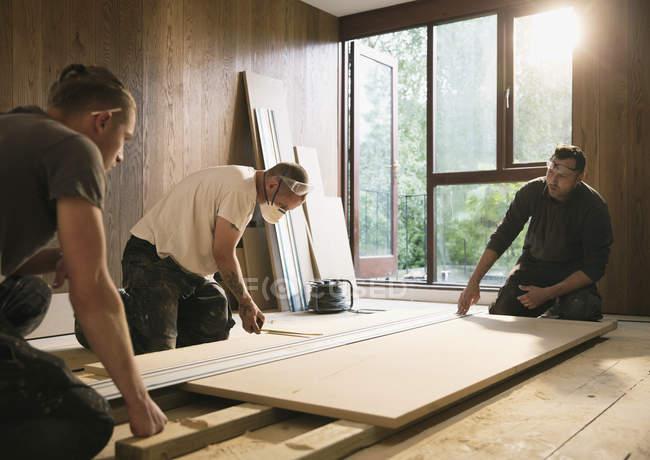 Trabalhadores de construção medindo placa de madeira — Fotografia de Stock