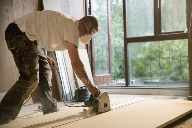Construction worker using electric saw to cut wood board in house — Stock Photo