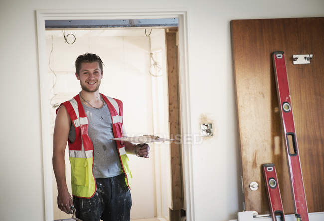 Portrait smiling construction worker plastering in house — Stock Photo