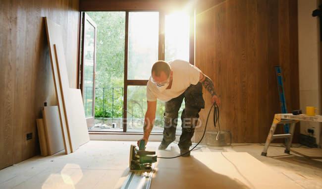 Строитель, использующий электропилу для резки древесины в доме — стоковое фото