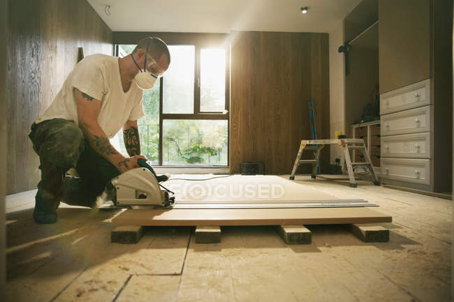 Construction worker with tattoos using table saw to cut wood board in house — Stock Photo