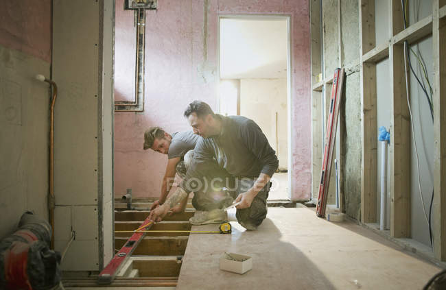 Строители используют инструмент уровня в доме — стоковое фото