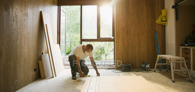 Construction worker measuring wood board in house — Stock Photo