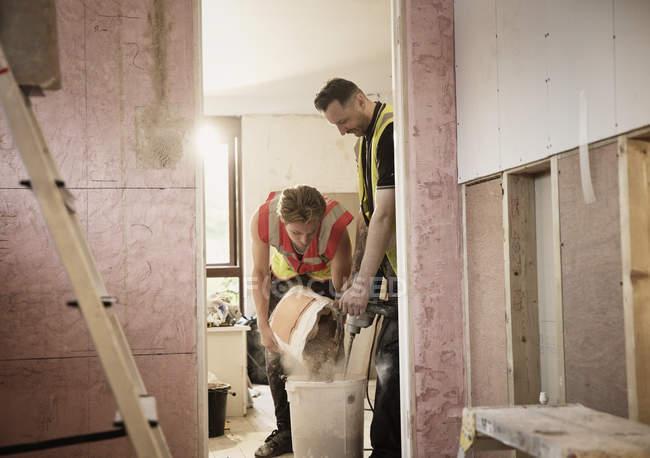 Строители смешивают штукатурку в доме — стоковое фото