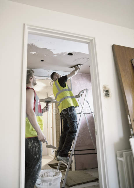 Construction workers plastering ceiling in house — Stock Photo