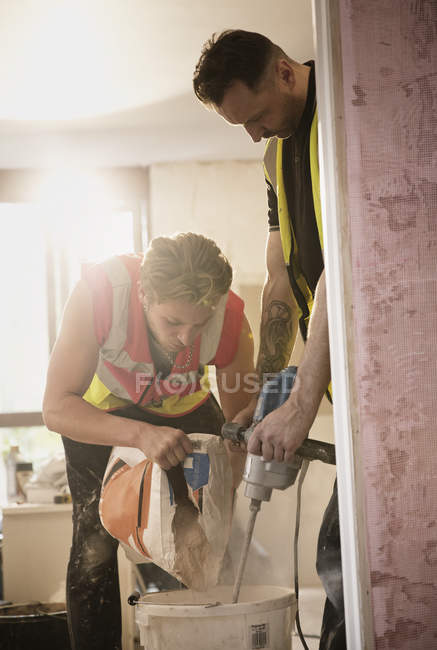 Construction workers mixing plaster — Stock Photo