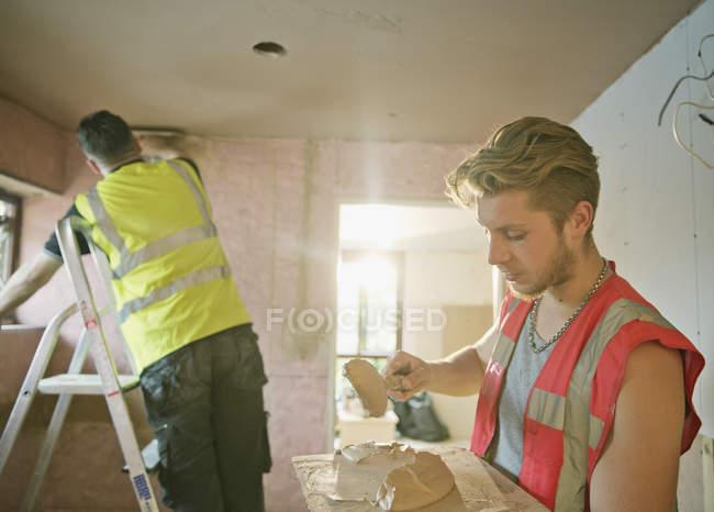 Trabalhadores da construção civil reboco na casa — Fotografia de Stock
