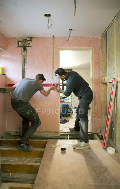 Construction workers using level tool in house — Stock Photo