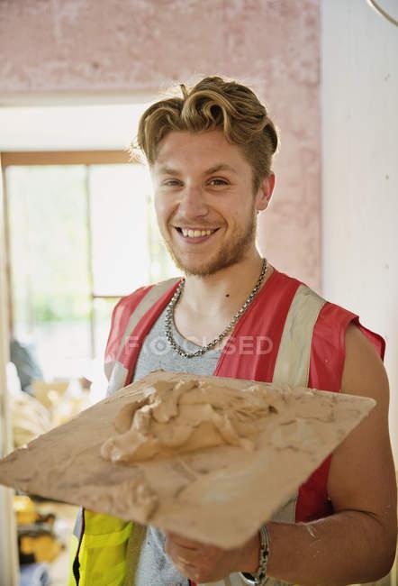 Retrato sorridente, confiante jovem trabalhador da construção civil reboco — Fotografia de Stock