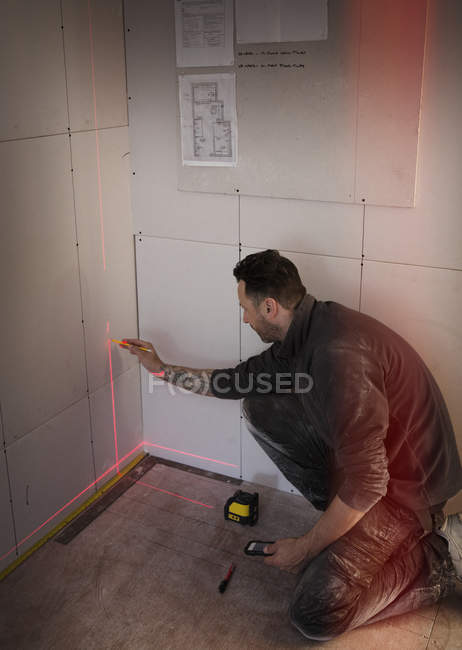 Construction worker using laser measuring tool — Stock Photo