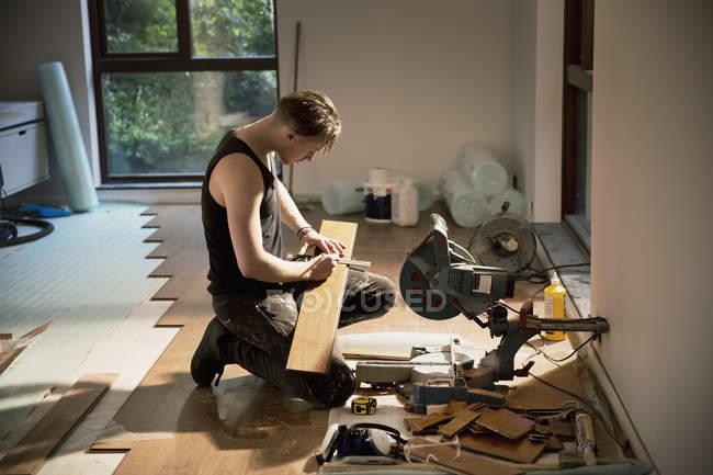 Строитель готовит паркетные полы в доме — стоковое фото