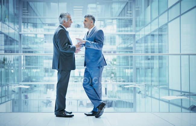 Бізнесмени говорять на сучасний офіс атріуму балкон — стокове фото