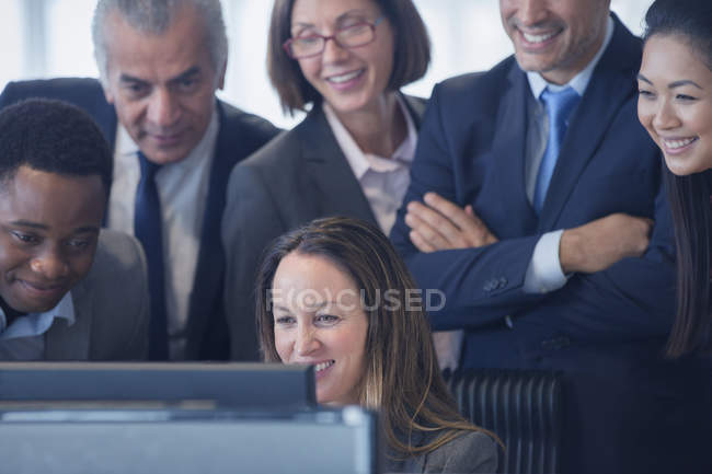 Smiling business people working at computer in office — Stock Photo