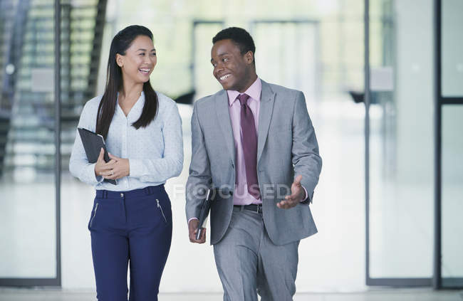 Smiling business people walking and talking — Stock Photo