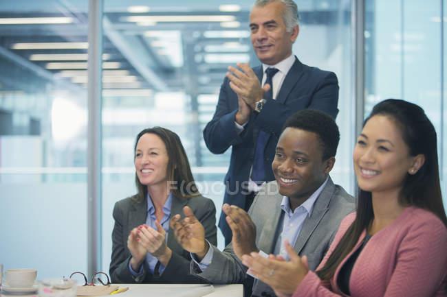 Ділові люди посміхаються і плескали на засіданні конференц-залу — стокове фото