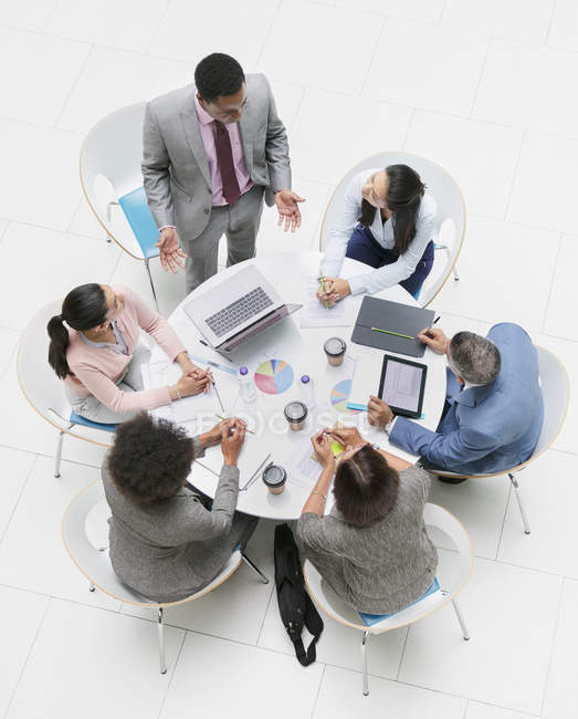 High angle view businessman leading meeting at round table — Stock Photo