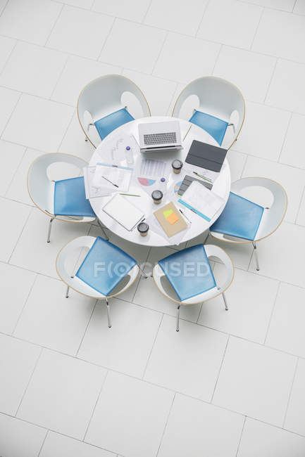 High angle view business laptop and paperwork on round table — Stock Photo