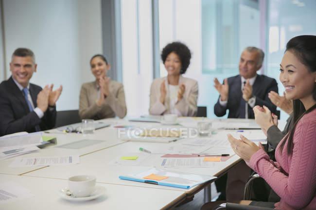 Gens d'affaires souriant frappant en séance salle de conférence — Photo de stock