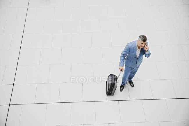 Hochwinkel-Geschäftsmann mit Koffer telefoniert — Stockfoto