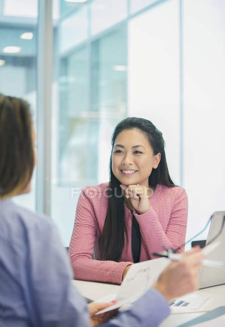 Smiling, attentive businesswoman listening to colleague in meeting — Stock Photo