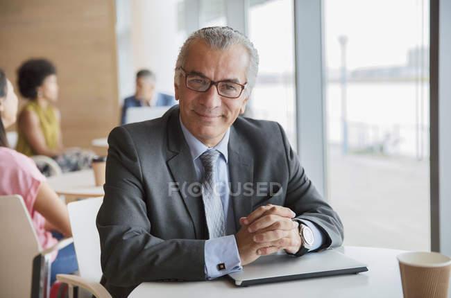 Portrait confident businessman in cafeteria — Stock Photo