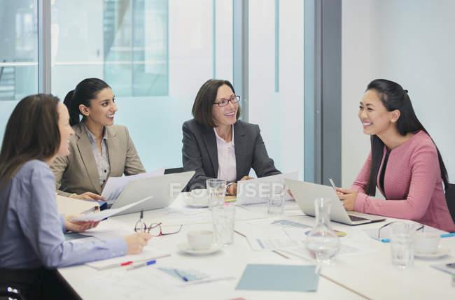 Des femmes d'affaires souriantes parlent en salle de conférence — Photo de stock