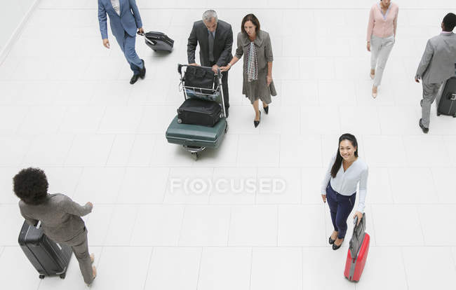 High angle portrait smiling businesswoman with suitcase in airport — Stock Photo