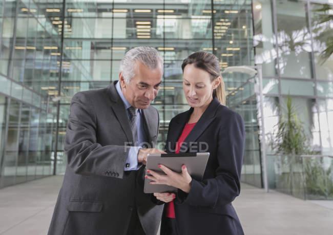 Geschäftsleute nutzen digitales Tablet vor modernem Bürogebäude — Stockfoto