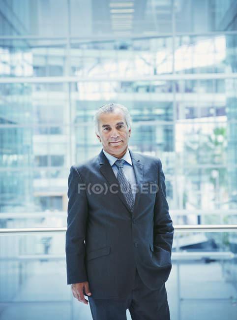 Portrait homme d'affaires senior confiant sur le balcon de l'atrium de bureau moderne — Photo de stock