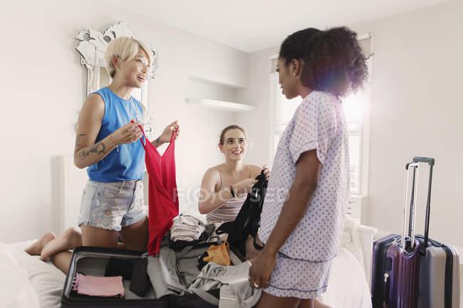 Giovani donne amici imballaggio per Spring Break in appartamento camera da letto — Foto stock