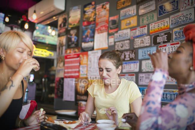 Young women friends taking tequila shots in bar — Stock Photo